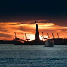sunrise behind the statue of liberty